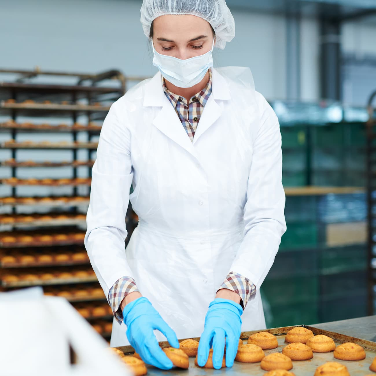 confectioner-collecting-freshly-baked-pastry-from--PUFKGJC